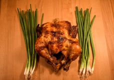Roasted Chicken Garnished With Green Scallions On Each Side On Wood Table. Whole roasted chicken with green scallion vegetables on each side served on a wood Stock Image
