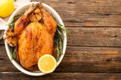 Whole roasted chicken with lemon and rosemary on a black plate. Rustic style. Christmas concept. Christmas turkey. stock photography