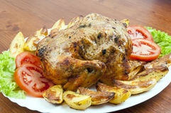 Whole roasted chicken. On plate with vegetables Royalty Free Stock Photo