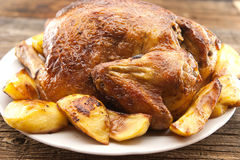 Whole roasted chicken with potatoes on rustic wooden table. Sele Stock Photos