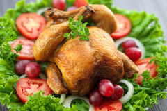 Whole roasted chicken. Served on a green leaf lettuce bed garnished with grapes, sliced onions, sliced tomatoes, parsley and a fresh oregano sprig Stock Photo