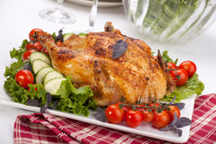 Whole roasted chicken on table Royalty Free Stock Photos