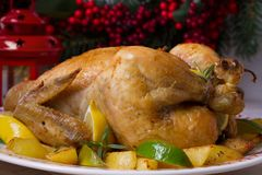 Whole roasted chicken or turkey with potatoes, lemons and limes. On Christmas and New Year background, horizontal Stock Photo