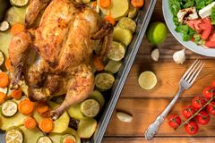 Whole roasted chicken and vegetables. On the wooden table. Top view Stock Image