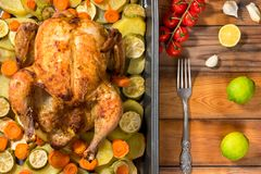 Whole roasted chicken and vegetables. On the wooden table. Top view Royalty Free Stock Photo