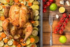 Whole roasted chicken and vegetables. On the wooden table. Top view Stock Photos