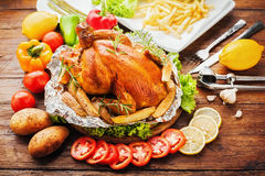 Whole roasted chicken with vegetables. On wood table Royalty Free Stock Photography