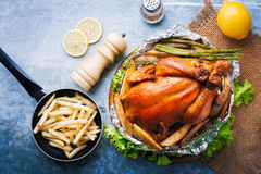 Whole roasted chicken with vegetables. On wood table Stock Photo