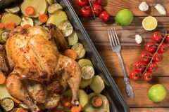 Whole roasted chicken and vegetables. On the wooden table. Top view Stock Photography