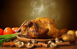 Whole roasted chicken with vegetables. On wooden tray fresh from oven with hot steam smoke, brown background