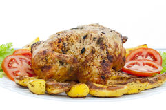 Whole roasted chicken on white background. Whole roasted chicken on plate with vegetables, isolated Royalty Free Stock Photos