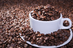 Whole roasted coffee beans in bowl. And glass and wood table Royalty Free Stock Image