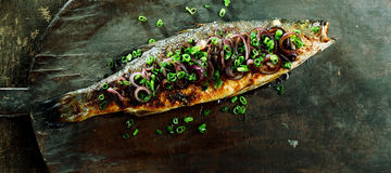 Whole Roasted Fish Garnished with Onions Stock Photography