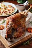 Whole roasted lamb leg on wooden cutting board. Roasted lamb leg served on wooden cutting board with grilled carrots and assorted appetizers stock photo