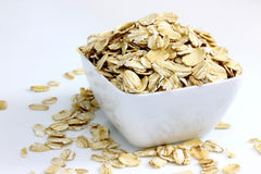 Whole Rolled Oats in White Bowl. Closeup of Whole Rolled Oats in White Bowl on white royalty free stock photography