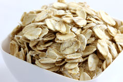 Whole Rolled Oats in White Bowl. Extreme Closeup of Whole Rolled Oats in White Bowl on white stock image