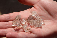 Whole rough silicon dioxide crystal quartz in hand Royalty Free Stock Image
