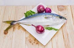 Whole round fish yellowtail and red onion on a wooden surface Stock Photos