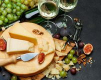 Whole round Head of parmesan or parmigiano hard cheese and wine. On concrete background or table Royalty Free Stock Image