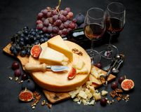 Whole round Head of parmesan or parmigiano hard cheese and wine. On concrete background or table Royalty Free Stock Photo