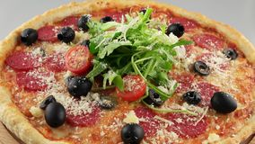 Whole salami pizza with cherry tomatoes stock video footage