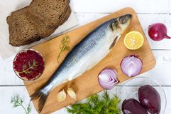 Whole salted herring with boiled beet, red onion, garlic, lemon, dill, rye bread. Royalty Free Stock Images