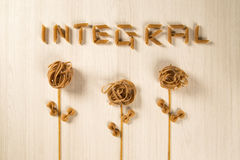 Whole-shaped integral pasta with flowers on a white wooden table.  royalty free stock photo