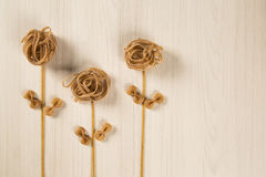Whole-shaped integral pasta with flowers on a white wooden table.  stock photography
