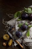 Whole and slice prunes with leafs on rustic background Royalty Free Stock Photo