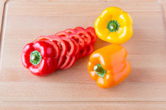 Whole and sliced bell peppers on wooden cutting board. Royalty Free Stock Photos