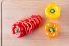 Whole and sliced bell peppers on wooden cutting board. Stock Image
