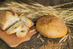 Whole and sliced bread with ears and wheat grain Royalty Free Stock Photos