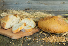 Whole and sliced bread with ears and wheat grain Royalty Free Stock Photography
