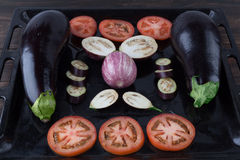 Whole and sliced eggplants and tomatoes on baking tray Stock Photo