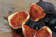 Whole and sliced figs and black grapes Stock Photos