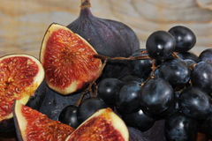 Whole and sliced figs and black grapes Royalty Free Stock Photos