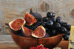 Whole and sliced figs and black grapes Royalty Free Stock Images