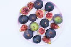 Whole and sliced figs on a pink plate on white background. stock photos