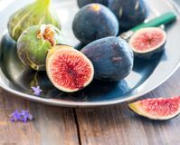 Whole and sliced figs on a plate and on a wooden table. Beautiful still life. Stock Images