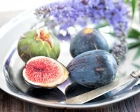 Whole and sliced figs on a plate and on a wooden table. Beautiful still life. Royalty Free Stock Photo