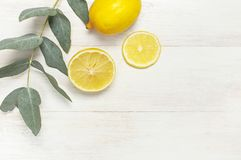 Whole and sliced fresh lemon, eucalyptus leaves on white wooden background. Flat lay, top view, copy space. Minimal fruit concept. Design. Yellow citrus lemons royalty free stock photos