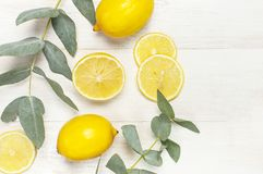 Whole and sliced fresh lemon, eucalyptus leaves on white wooden background. Flat lay, top view, copy space. Minimal fruit concept. Design. Yellow citrus lemons stock image