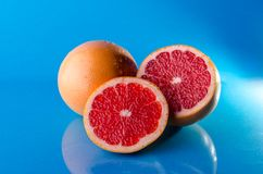 Whole sliced grapefruit on a blue background, horizontal shot. Picture presents Whole sliced grapefruit on a blue background, horizontal shot Royalty Free Stock Image