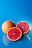 Whole sliced grapefruit on a blue background, vertical shot. Picture presents Whole sliced grapefruit on a blue background, vertical shot Royalty Free Stock Photography