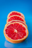 Whole sliced grapefruit on a blue background, vertical shot. Picture presents whole sliced grapefruit on a blue background, vertical shot Stock Image