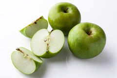Whole and sliced green apples from side high angle white Royalty Free Stock Images