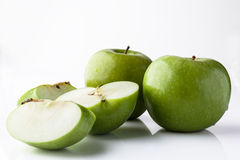 Whole and sliced green apples from side on white Stock Image