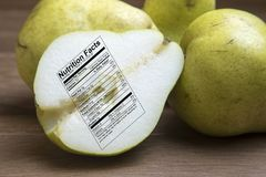 Whole and sliced green pears with nutrtional label on wooden boa Royalty Free Stock Images