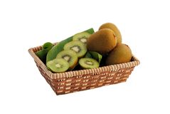 Whole and sliced kiwi in a straw basket Stock Image
