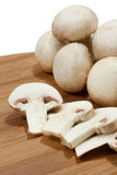 Whole and sliced mushrooms on wooden board Stock Images
